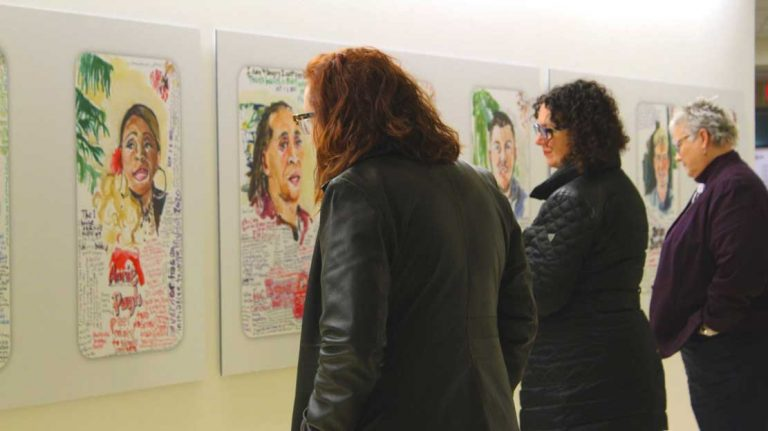 People observing Charmaine's portraits on the wall