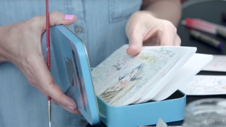 Charmaine's hands holding a tin of watercolor portraits